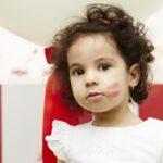 Little girls with lipstick on cheek