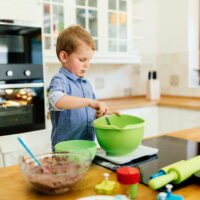Child helping mother make cookies as a professional chef