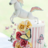 Jumping unicorn birthday cake with flowers and butterflies