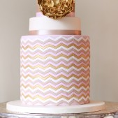 gold rose cake on silver stand and candle vertical
